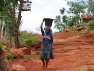 mulher carrega balde água no sertão