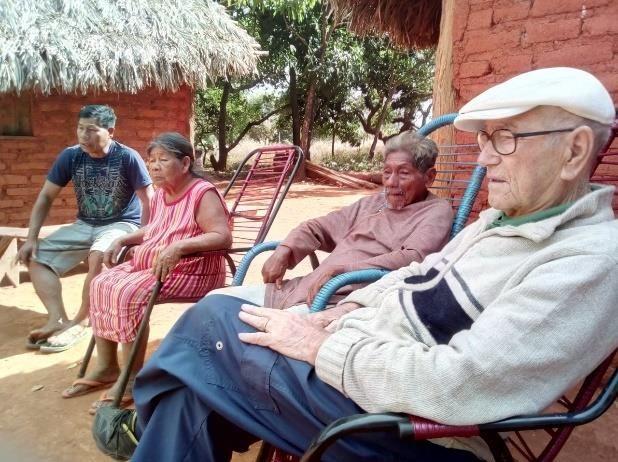 Rinaldo sentado numa cadeira em frente a anciãos indígenas