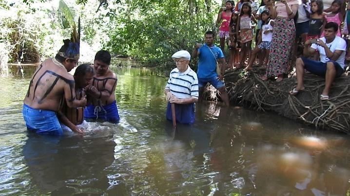 Indígenas batizam um parente enquanto Rinaldo e outros indígenas observam