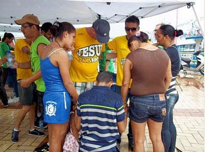 Equipe de voluntários ora com participantes do Festival de Parintins (AM).